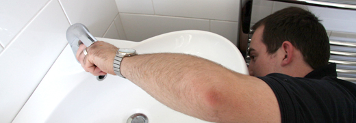 plumber reconnects sink drain while holding faucet